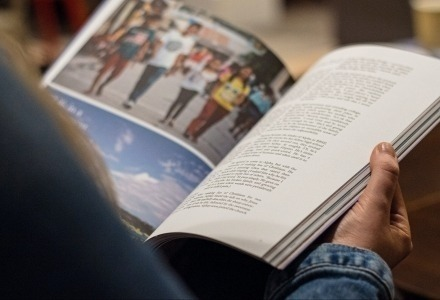A person is holding a publication open with colour photos and writing